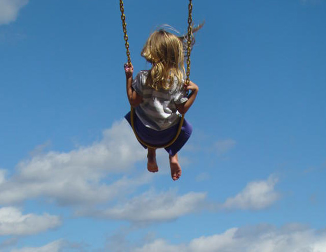 Swinging on a swing set is a fun summer vacation activity