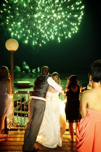 Wedding party enjoying festive fireworks display at Cragun's Resort lakeside deck