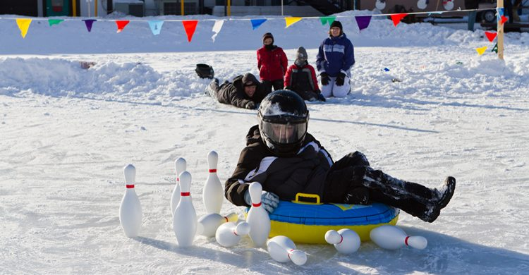 Child knocking down bowling pins on a sled while playing in the snow at Cragun's Resort in Brainerd, MN.
