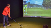 Golfer practicing on indoor golf simulator at Cragun's Golf Legacy